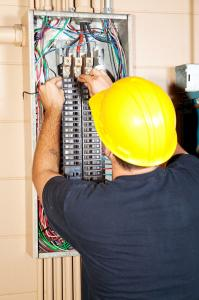 electrician working on a fuse box